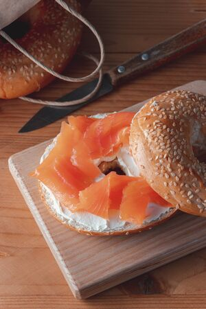 Fresh made Bagel with Salmon on old wooden table. Stock Photo - 147526395