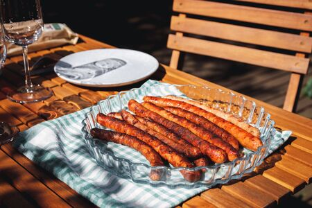 Pork chipolata. Close-up view of fried sausages. Meat dish.