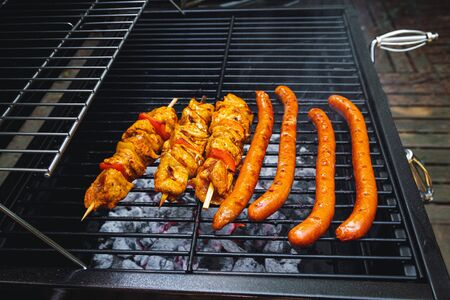 Meat skewers and sausages being grilled on a barbecue.