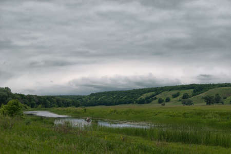 riverside trees: Fisherman in a boat on a small lake in a cloudy hilly valley