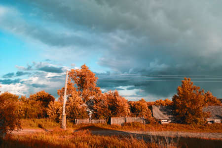 overcast: The storm clouds approaching the village autumn street Stock Photo