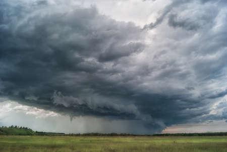 Sturmwirbelsturm über Sommerfelder, Hügel und Wälder. Standard-Bild - 81171980