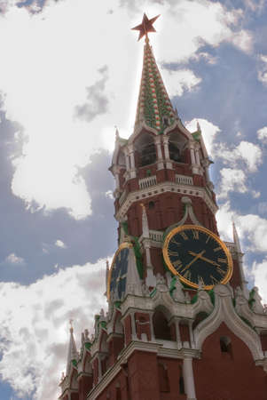Kremlin clock chimes close-up against a blue cloudy sky. Moscow.