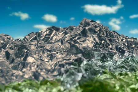 Texture of crumpled silvery gray metal foil with a dent close-up in the form of a mountain landscape with sky.