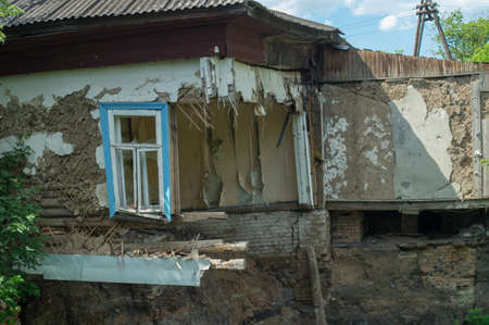 Ruined damaged building. Affected as a result of a natural disaster. A collapsed floor in the room of a private house, fragment of the wall and window. Destruction of the foundation by groundwater.