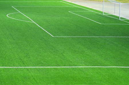 Fragment of a fresh green football field with a marking for the background
