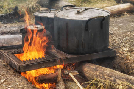 Field kitchen. Saucepan, pot and kettle on fire from the bonfire. Water boils and cooking food in the tourist camp