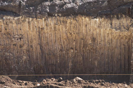 Texture of soil with traces of a bucket of excavator. Wall ground of section quarry pit for foundation building construction.