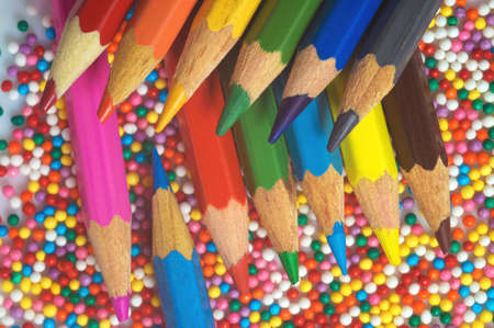 Color pencils on the background of the texture of multi-colored balls close-up. A set for children's creativity and development. Reklamní fotografie