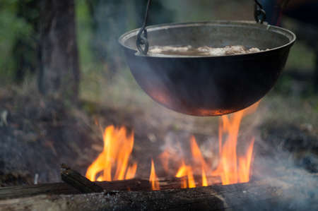 Pot with meat stew, on a fire bonfire in a tourist camp in a wild forest.