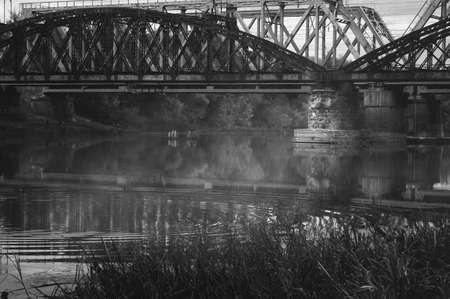 Black and white image of old railway bridges over the autumn foggy river. Gloomy atmospheric cityscape