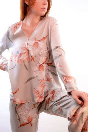 Beautiful booty of a young woman in fashionable beige pajamas Banque d'images