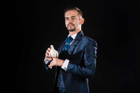 Handsome male magician with a suspicious look in a blue tailcoat holding a dove on a black background