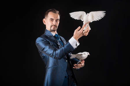 A magician in a blue tailcoat holds two white doves in his hands on a black background