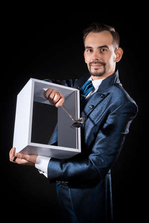 Male magician on a black background holding a focus box and a ladle