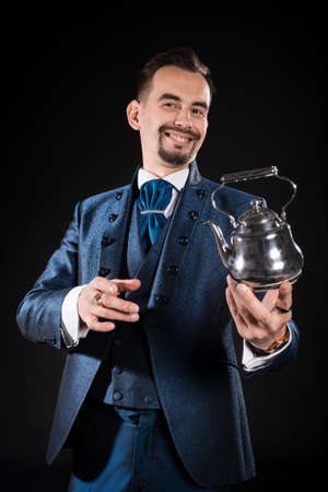 Handsome magician with a smile in a blue tailcoat holds a magic teapot in his hand