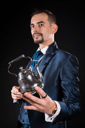 A handsome magician in a blue dress coat holds a magic teapot in his hand