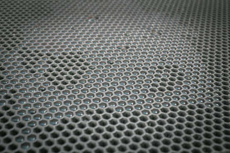 Gray rubber mat with honeycombs in which transparent water drops glisten Banque d'images