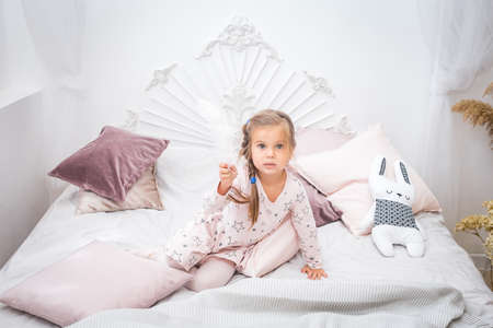Little girl in a pink dress sits on the bed and holds a large white feather in her hands.