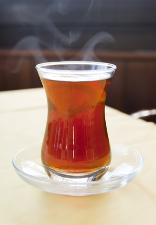 Hot turkish tea with lemon in traditional glass photo