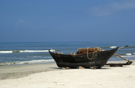 Goa: Traditional indian fishing-boat in wild beach. South goa.India