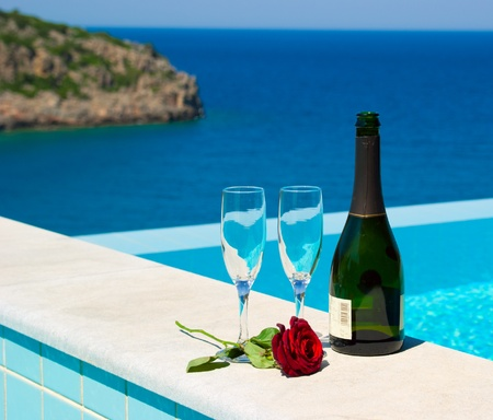 在豪华地中海度假村的无边泳池附近的浪漫野餐。香槟和玫瑰。希腊