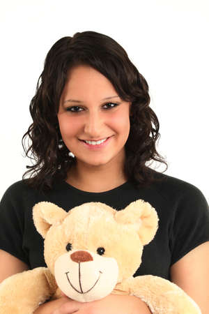 Young teenage girl is holding teddy and keep smiling