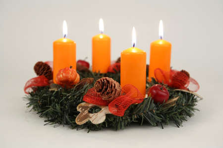 Advent wreath with four orange candles and decorations