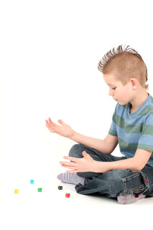 spiked hair: Portrait of young boy with mohawk playing with dice, studio shot Stock Photo