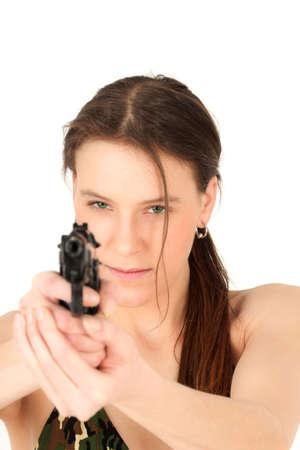 Portrait of young woman aiming gun, studio shot photo