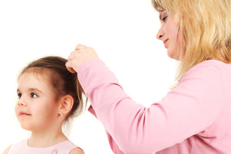 Portrait of mother helping daughter with hair, studio shot