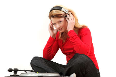Portrait of young woman listening to record with headphones, studio shot photo