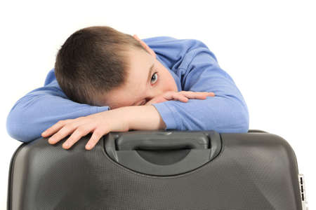 Portrait of tired young boy leaning on suitcase, studio shot photo