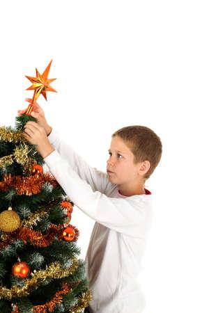 Young boy putting star on Christmas tree, studio shot photo