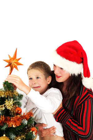 Mother and son putting star on Christmas tree, studio shot photo