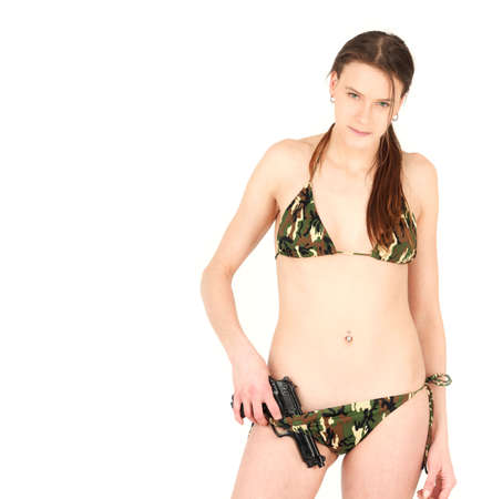 Portrait of young woman in bikini holding gun, studio shot photo