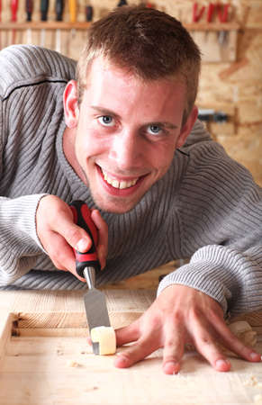 Young smiling carpenter mortising and smiling