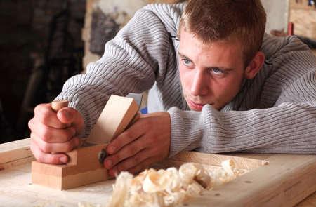 carpintero: Joven que trabaja con el plano Foto de archivo