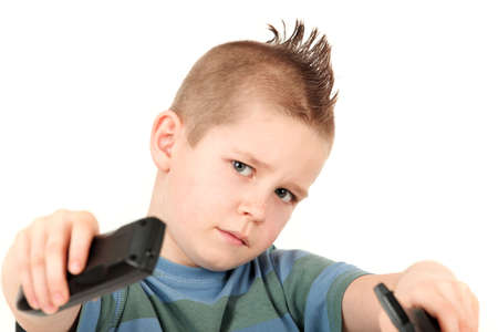 Portrait of young boy with mohawk holding remote controls, studio shot
