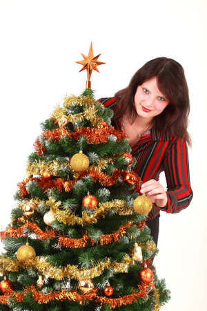 decorating christmas tree: Portrait of young woman decorating Christmas tree, studio shot Stock Photo