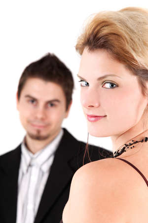 looking over shoulder: Portrait of young beautiful woman looking at camera, man in background Stock Photo