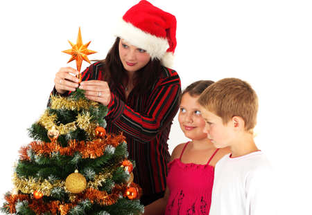 Mother and children decorating Christmas tree, studio shot photo