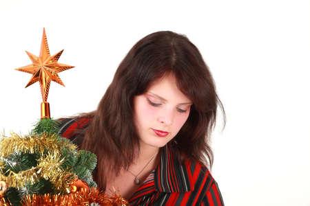 Portrait of young woman decorating Christmas tree, studio shot photo