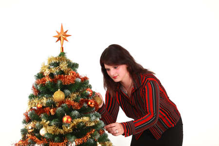 Portrait of young woman decorating Christmas tree, studio shot photo