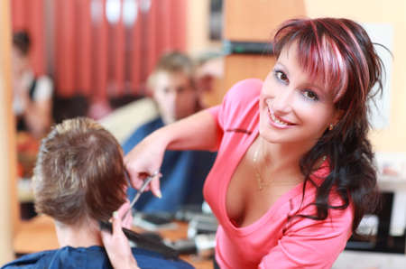 Portrait of young hairdresser smiling and cutting hair Stock Photo