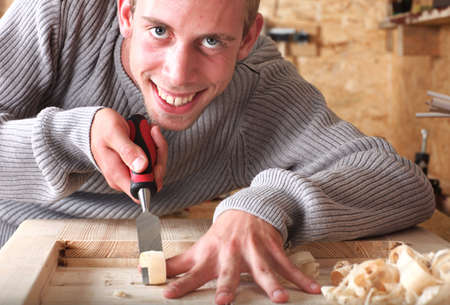Young carpenter with gad working and smiling Stock Photo - 6068407