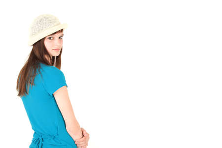 Rear view of young teenage girl in blue shirt and hat, studio shot