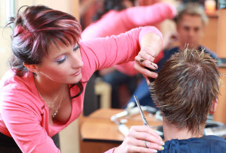 Portrait of professional haidresser cutting young males hair