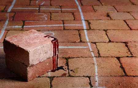Blood covered brick at scene of crime or accident with numbered chalk markings. Stock Photo