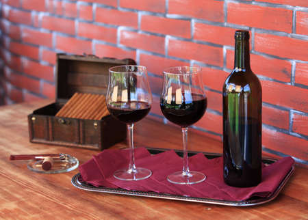 Two glasses of red wine with bottle and open box of cigars.